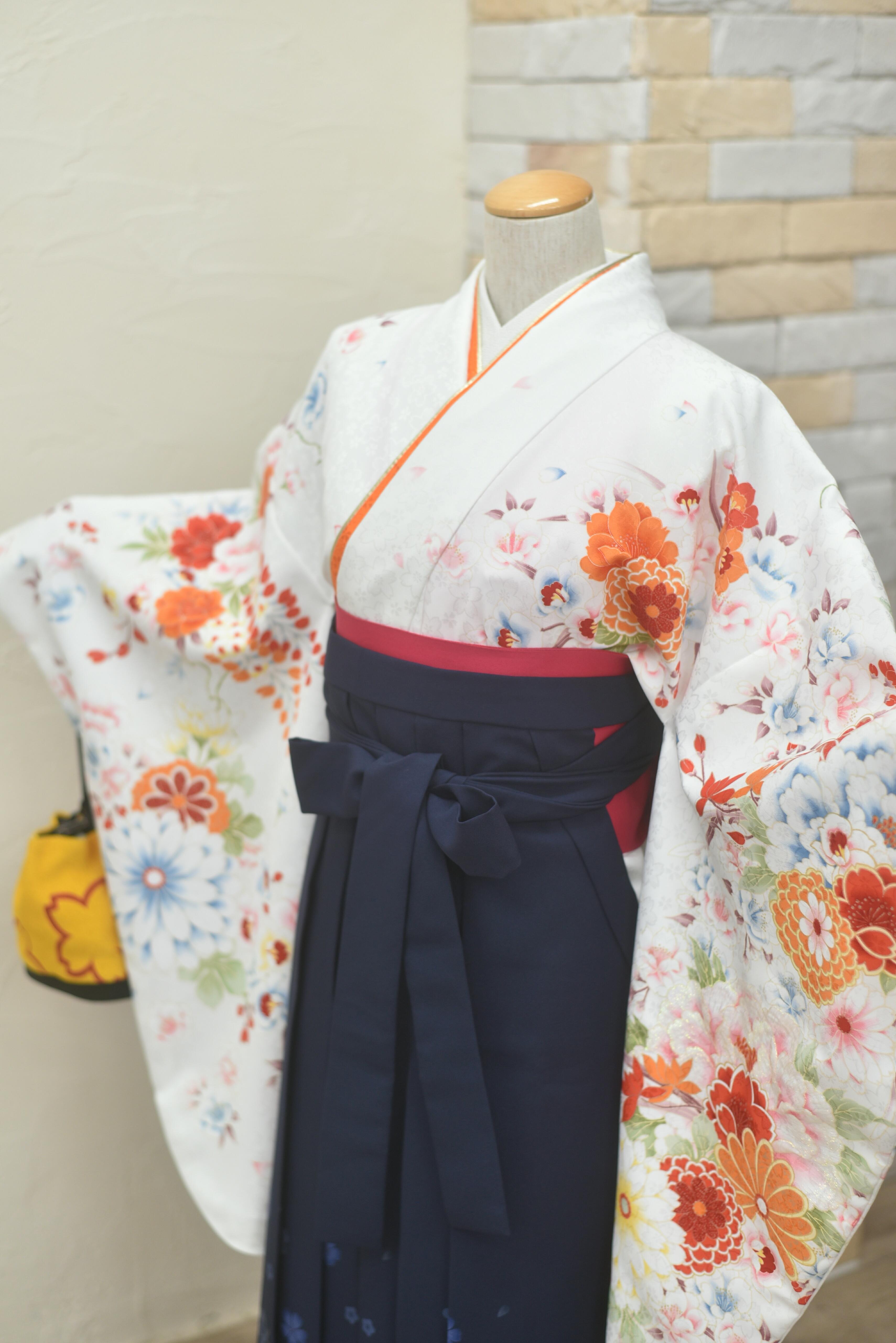 白地にオレンジ赤花柄、紺の袴胸元アップ