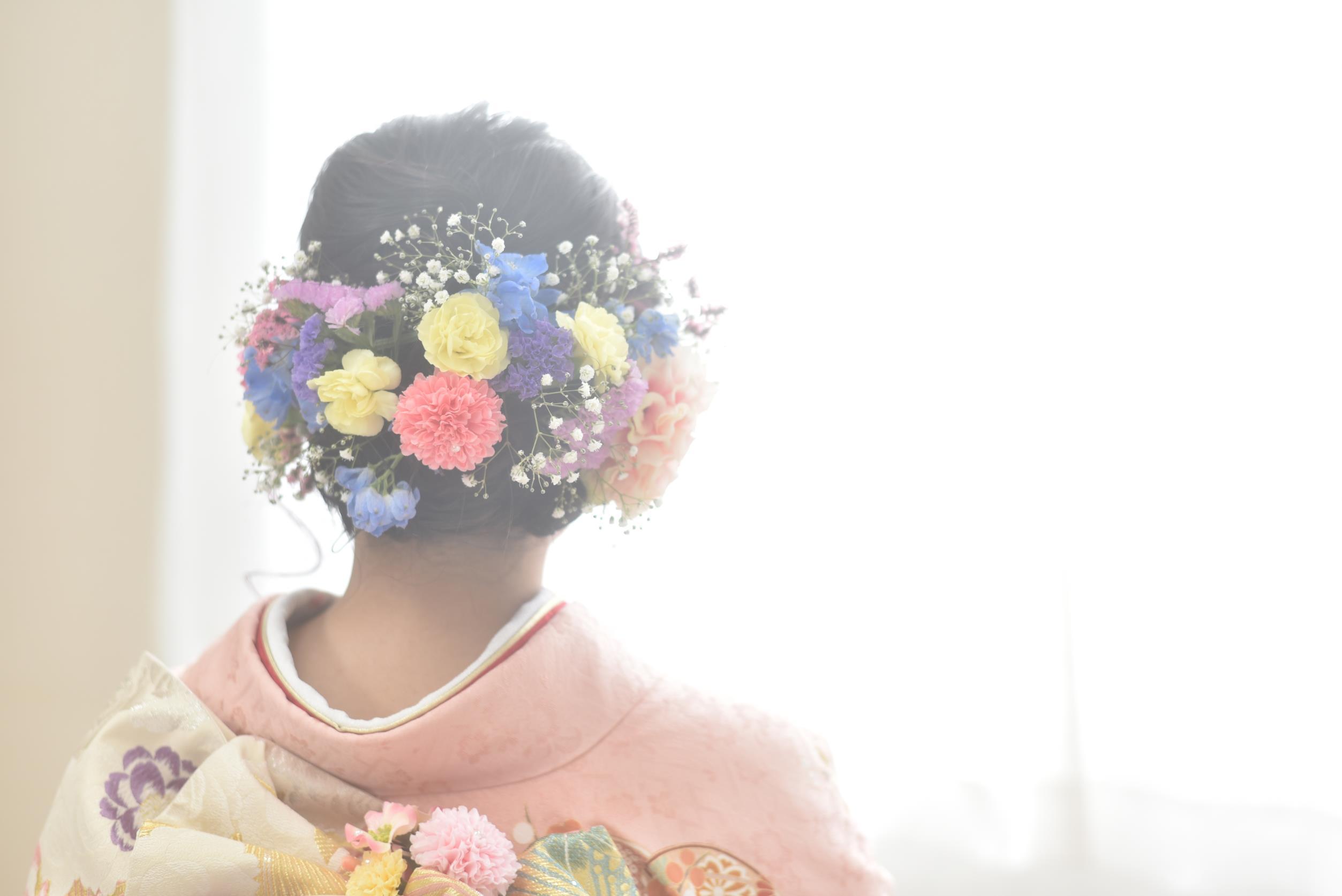 ピンクの振袖を着た女性の生花を使ったヘアスタイル