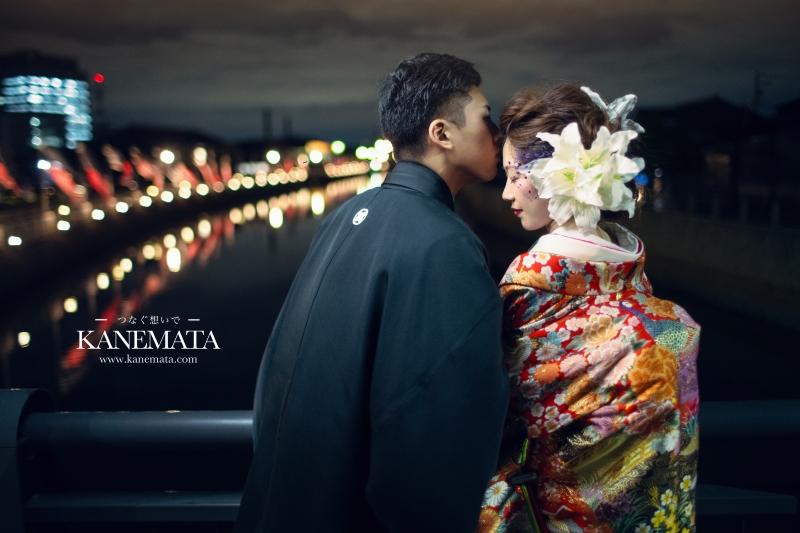 夜の橋の上で紋付袴、色打掛を着た男女