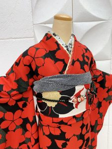 黒地に赤の桜柄の振袖。帯や半襟、帯揚げ帯締め重ね衿も全て赤白黒で統一されている