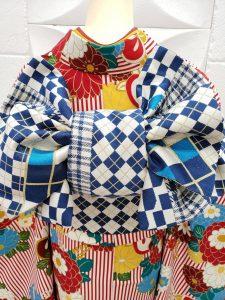 白に赤のストライプと花柄のレトロモダンな振袖コーデの後ろ姿。帯結びがよく見える。帯は白と青のチェック柄