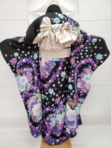 黒色に紫や蛍光緑で薔薇の花や星が大小たくさん描かれている成人式用振袖。人気の宇宙柄、星空っぽいコーディネート。袋帯はシルバーの無地