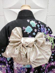 黒地に紫、ミントグリーンのバラ模様のfurisode。帯の結びがよく分かる後姿のマネキン写真