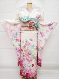 白地に裾はピンクのぼかし入りの薔薇柄振袖。マイメロディをテーマにコーディネートして水色の帯揚げや重ね衿を使用した可愛い一式