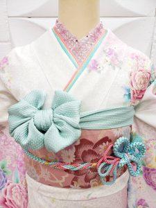 白地に裾はピンクのぼかし入りの薔薇柄振袖。マイメロディをテーマにコーディネートして水色の帯揚げや重ね衿を使用したかわいい一式(衿元アップ)