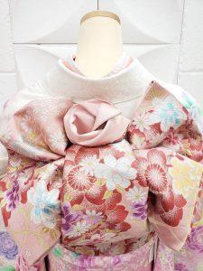 白地にピンクのぼかし入りのバラ柄furisode。マイメロディをテーマにコーデされたカワイイ組み合わせ。袋帯はサーモンピンクの花柄。帯結びがよく分かるマネキンの後姿
